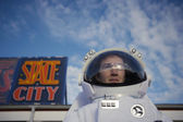 "Man in spacesuit leaving ""Space City"" — Stock Photo"