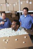Three male warehouse workers joking around — Stock Photo