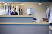 Asian businesswoman at drycleaner — Stock Photo