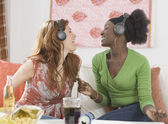 Two women singing to headphones — Stock Photo