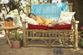 Hispanic girl laying on bench outdoors — Stock Photo
