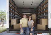 Portrait of couple sitting in moving truck — Stok fotoğraf