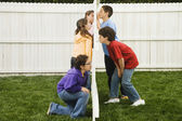 Mixed Race children looking at each other through fence — Foto Stock