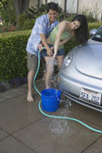 Young couple washing car together — Foto de Stock