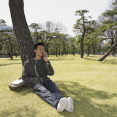 Asian man leaning on tree and using cell phone — Stock Photo
