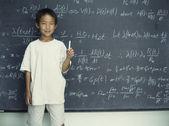 Portret van jongen houden krijt staande voor schoolbord — Stockfoto