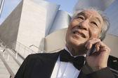 Cep telefonu kullanarak smokin kıdemli Asyalı adam — Stok fotoğraf