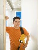 Male carpenter standing in doorway inside construction site — Stockfoto