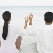 Couple meditating on the beach — Stock Photo