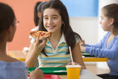 Four girls eating pizza in cafeteria — Stock Photo