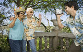 Young man using video camera to film senior couple waving — Stockfoto