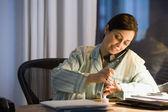 Hispanic businesswoman painting fingernails at desk — Stock Photo