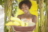Portrait of woman holding bowl of bananas — Stock Photo