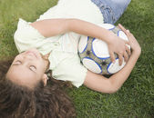 Young girl laying on ground with soccer ball — Stock Photo