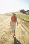 Young woman walking on a dirt road — Stock Photo