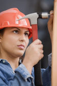 Hispanic female construction worker hammering a nail — Stock Photo