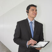 Mixed Race businessman writing in date book — Stock Photo