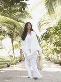 Young woman walking in tropical surroundings — Stock Photo