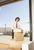 Businessman labelling cardboard boxes in a garage — Stock Photo