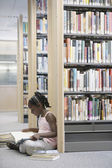 Girl reading book in library — Stock Photo