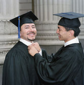 Graduate tying colleague's collar — Stock Photo