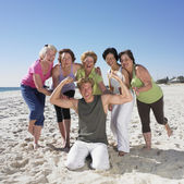 Group of senior women in athletic gear with young man on beach — Stock Photo