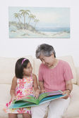Asian grandmother and granddaughter reading book — Stock Photo