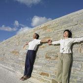 Pareja asiática apoyado en una pared al aire libre — Foto de Stock