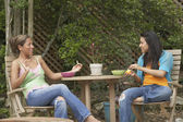Two young women eating together outside — Stock Photo