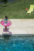 High angle view of girl standing on diving board with innertube — Stock Photo