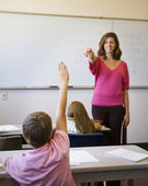 Female teacher calling on student in classroom — Stock Photo
