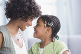 African American mother and daughter smiling at each other — Stock Photo