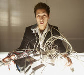 Businessman puzzling over a nest of wires — Stock Photo
