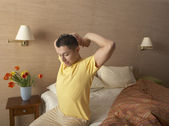 Man stretching on side of bed — Stock Photo