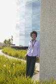 Businesswoman leaning against office building wall — Stock Photo