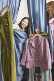 Kobieta z kurtyny z garderoba na ubrania — Zdjęcie stockowe