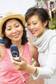 Two women taking picture with cell phone — Stock Photo