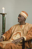 African man wearing traditional dress sitting next to lit candle — Stock Photo