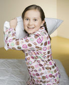 Portrait of girl having pillow fight — Stock Photo