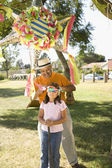 Hispanic girl being blindfolded next to pinata outdoors — Stock Photo