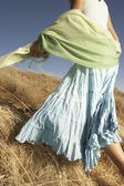 Woman in a flowing skirt walking through tall grass — Stock Photo