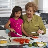 Hispanic grandmother and granddaughter preparing food — Foto Stock