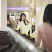 Young woman looking at new clothes in mirror — Stock Photo