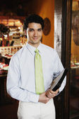 Portrait of waiter holding menus in restaurant — Stock Photo