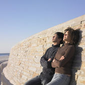 Young couple relaxing against a wall — Stock Photo