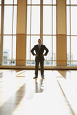 Businessman standing in sunlit room with hands on his hips — Stock Photo