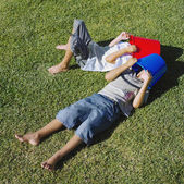 Two boys laying on grass with buckets on heads — Stock Photo