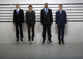 Multi-ethnic businessmen jumping in police line up — Stock Photo