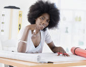 African female architect looking over blueprints — Stock Photo