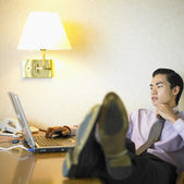 Businessman typing on laptop with feet on desk — Stock Photo